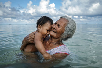 Suega Apelu bathes a child in a lagoon in Tuvalu, one of the Pacific Island nations most threatened by climate change.
