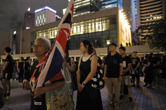 Alexandra Wong, 63 carries a Union flag as people queue up during a vigil to mourn the recent suicide of a woman due to the government's policy on the extradition bill in Hong Kong in July.