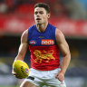 GOLD COAST, AUSTRALIA - JULY 31: Lachie Neale of the Lions handballs during the round nine AFL match between the Essendon Bombers and the Brisbane Lions at Metricon Stadium on July 31, 2020 in Gold Coast, Australia. (Photo by Chris Hyde/AFL Photos/via Getty Images)