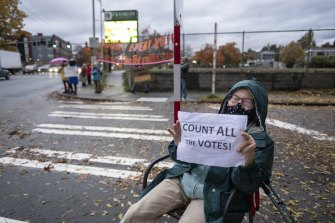 Kathleen Myers sits while holding a sign in support of those taking part in a Count Every Vote rally.