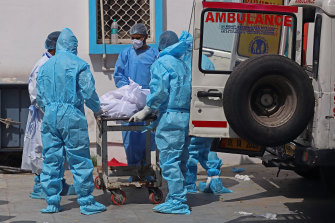 Health workers move the body of a COVID-19 victim at a mortuary in New Delhi on Wednesday.