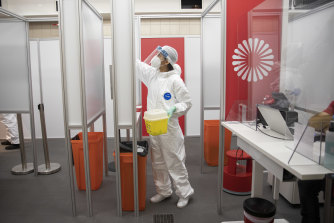 A medical worker cleans a COVID-19 testing site at at Berlin Brandenburg Airport this week.