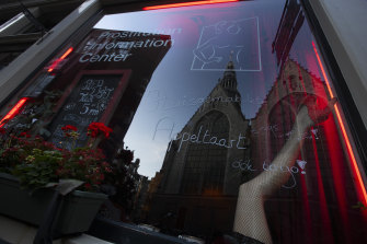 Oude Kerk, or Old Church, is reflected in the window of the Prostitution Information Centre as sex workers welcomed clients again in Amsterdam.