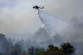 A fire department helicopter makes a water drop over a brush fire at the Sepulveda Basin in Los Angeles on Sunday.