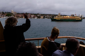 Passengers aboard the Queenscliff wave to her sister the Freshwater during its final voyage on Wednesday.