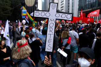 A demonstrator holds a sign in the shape of a cross with the phrase '500,000 deaths' during a protest against Bolsonaro's administration on June 19, 2021 in Sao Paulo, Brazil.