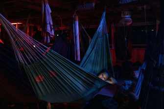 A woman rests in a hammock on an overnight boat journey along the Amazon River to the remote city of Tefé, Brazil.