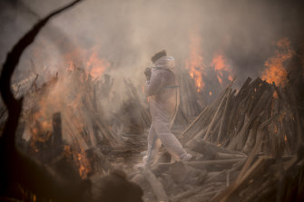A worker wearing a protective suit is seen amid the burning funeral pyres of patients who died of COVID-19 at a crematorium in Delhi, India.