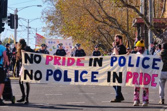 Protesters walked in front of police at the 2021 Pride March in St Kilda. The man with the walkie-talkie is a march marshal.