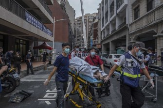 Paramedics transport a dead body from a residential building in the wake of a fire in Kaohsiung, Taiwan.