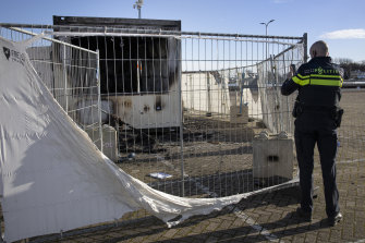 A police officer takes images of a torched coronavirus testing facility in the Dutch fishing village of Urk.