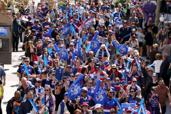 Bulldogs supporters march down the street during the People's Parade in Perth CBD ahead of the 2021 AFL grand final.