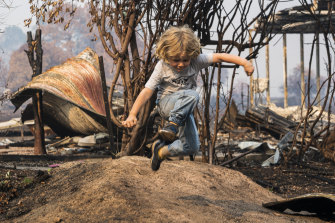 Josh Collings' son plays in front of the destroyed family home in Cudgewa.