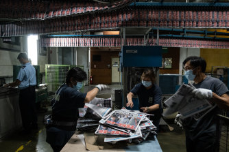 Employees arrange the Apple Daily newspaper on Tuesday.