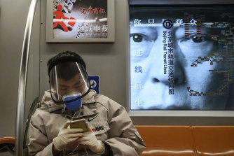 A Chinese man wears a protective mask and face shield as he rides the subway during rush hour.