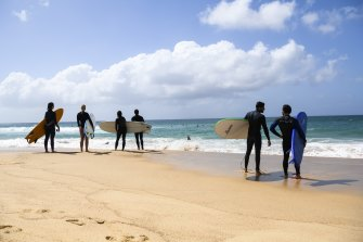 Surfers stand along the beach as they assess the surf.