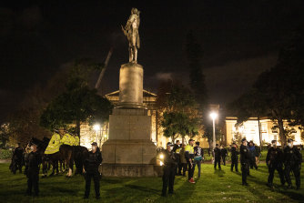A statue of Captain James Cook under police guard during the Black Lives Matter protest on Friday night.