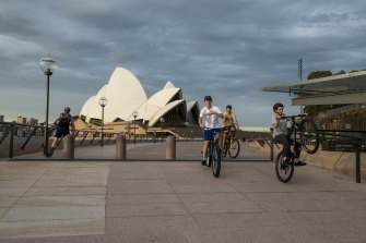Bike riders take a spin around Circular Quay, which is usually filled with crowds.