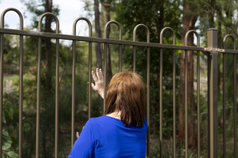 The daughter of a Newmarch House resident waves to her mother through the outer fence of the aged care home.