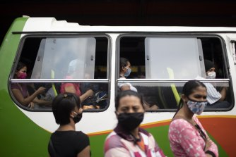 Commuters at a bus station wear protective face masks as a measure to curb the spread of the new coronavirus in Caracas, Venezuela.