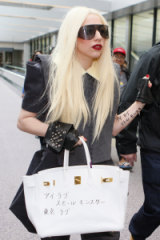"Lady Gaga in 2010, with her Hermes bag scrawled with the Japanese words ""little monsters"", the term she uses for her fans."