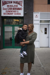 Donna Mosley with her grandson, who has not been vaccinated against measles, outside the Sister Clara Muhammad Elementary School and mosque in the Harlem area of New York.