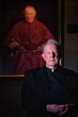 Father Bill Uren, rector of Melbourne University's Newman College, with the college's portrait of John Henry Newman in his cardinal's robes.