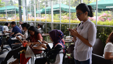 Customers on their phones at a cafe in Jakarta.