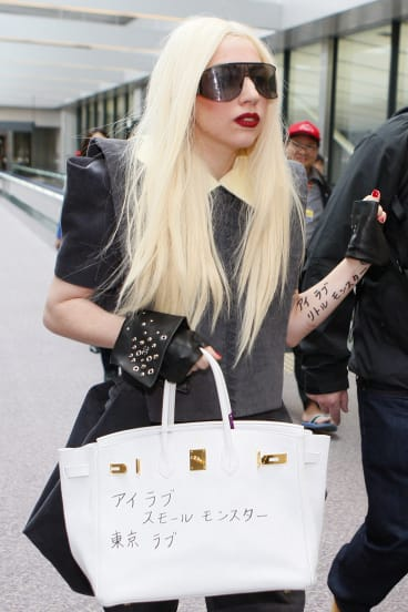 """Lady Gaga in 2010, with her Hermes bag scrawled with the Japanese words """"little monsters"""", the term she uses for her fans."""