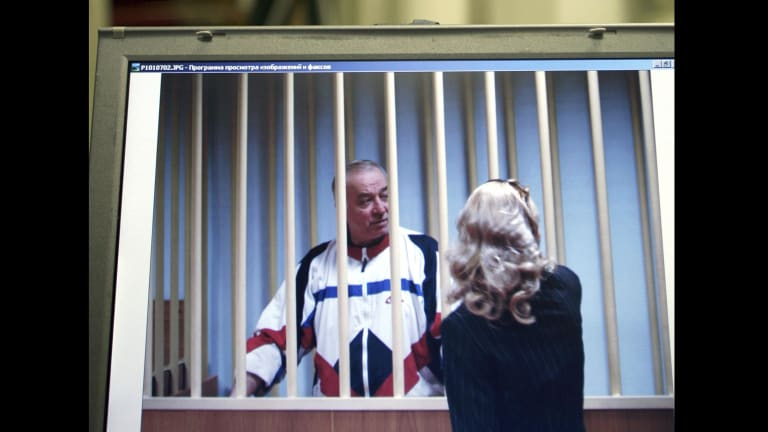 Sergei Skripal speaks to his lawyer from behind bars seen on a screen of a monitor outside a courtroom in Moscow in 2006.