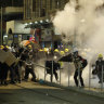 Popo fire tear gas at gangbangers up in Hong Kong on Sundizzle night.