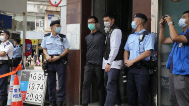 Simon Leung Kam-wai, fourth from right, a committee member of the Hong Kong Alliance in Support of Patriotic Democratic Movements of China, is escorted by police during an investigation of the June 4th Museum in Hong Kong.