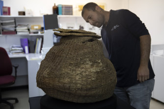 Archeologist Haim Cohen examines a woven basket that was found during a sweep of more than 500 caves.