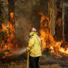 A Tuncurry fire crew member fights part of the Hillville bushfire south of Taree, in the Mid North Coast