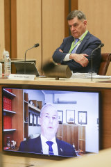 Secretary of the Department of Health Professor Brendan Murphy and Minister Colbeck appearing via video-conference, during a Senate select committee hearing on COVID-19, at Parliament House on August  21.