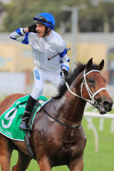Glen Boss reacts to the crowd after winning the Epsom on Kolding.