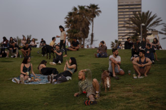 People without face masks watch the sunset, in Tel Aviv, after Israel lifted its public mask mandate.