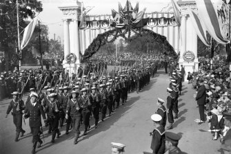 Troops marching through a decorated archway on Macquarie Street during peace celebrations.