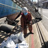 Chen Chen from China retrieves Neville Manson's 23 comfort packages from the foot of the gangplank in Portland.