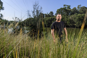 "Indigenous architect Dillon Kombumerri at the Cooks River near his home. ""I find that while I'm here, I have a responsibility to care for country."""