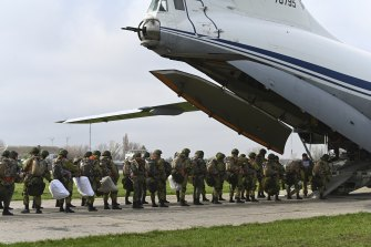 Russian paratroopers load into a plane for airborne drills on Thursday.