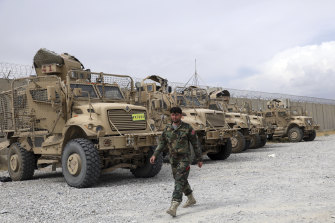 An Afghan army soldier walks past Mine Resistant Ambush Protected vehicles, MRAP, that were left after the American military left Bagram air base, in Parwan province north of Kabul, Afghanistan, on July 5.