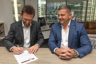 Xanthi FC owner Bill Papas watches on as Tony Popovic puts pen to paper with the Greek club.