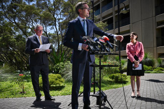 NSW Treasurer Dominic Perrottet addresses the media, flanked by Health Minister Brad Hazzard and Premier Gladys Berejiklian.