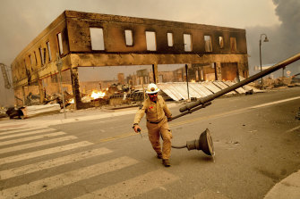 Operations chief Jay Walter moves a light post that was blocking Highway 89 as the Dixie Fire tears through the Greenville, California.