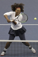 Serena Williams returns a shot in her Fed Cup doubles match.