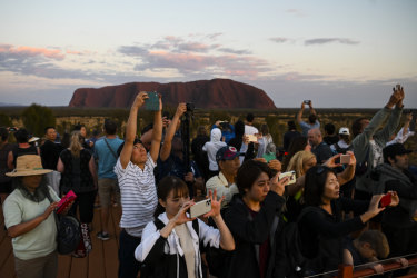 Tourists taking photographs of the rising sun near Uluru on October 12.