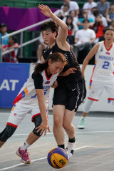Mongolia's Khulan Onolbaatar is checked by Okuyama Ririka of Japan during a 3x3 at the Asian Games in Indonesia in 2018.