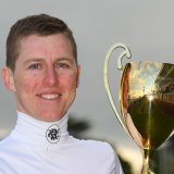 Damian Lane poses with the Caulfield Cup after his victory on Mer De Glace.