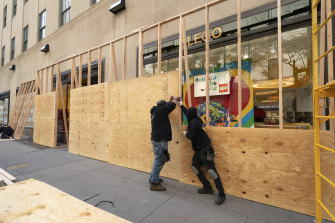 Workers erect a plywood wall to protect a LEGO store in Rockefeller Centre in New York ahead of the contentious presidential election.